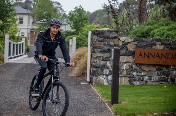 Sidharth rides a bicycle in picturesque Annandale, which gives an authentic New Zealand experience through the setting of a 4,000 acre coastal farm, farm-to-table local cuisine, numerous activities, historical significance and preservation of the buildings and local fauna, and interaction with locals.